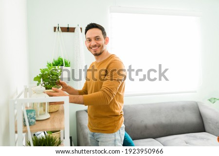 Portrait of a happy man smiling while holding a plant on a pot at home. Man with a positive mental health doing some gardening at home  Royalty-Free Stock Photo #1923950966