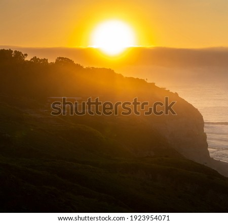 An idyllic view of the sun during sunset time on an idyllic beach with the cliffs silhouette illuminated by the sunlight. An amazing natural scene in Las Brisas beach Royalty-Free Stock Photo #1923954071