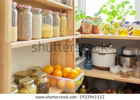 Kitchen pantry, wooden shelves with jars and containers with food, food storage. Jars of cereals, container of oranges, kitchen utensils, houseplants