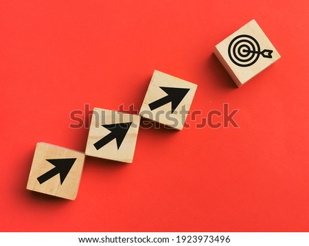 Target and focus concept. A bunch of wooden cubes line upward with arrow and dart target isolated on red background.