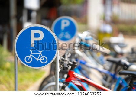Bike parking sign with a blurred bicycle background. Royalty-Free Stock Photo #1924053752