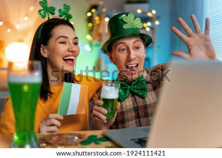 Happy family couple celebrating St. Patrick's Day with their friends by online at home. Royalty-Free Stock Photo #1924111421