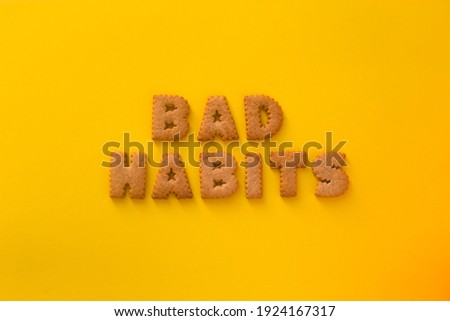 Word Bad Habits in the middle of the picture made of tasty crunchy cookies in form of English big alphabet letters, textured bright yellow background, health, dieting and medical concept. Copy space