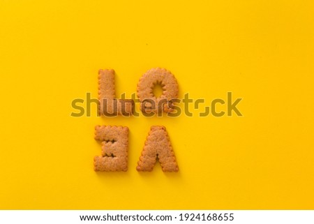 Word Love in the middle of the picture made of tasty crunchy cookies in form of English alphabet letters, textured bright yellow background, health, dieting and medical concept. Copy space big letters
