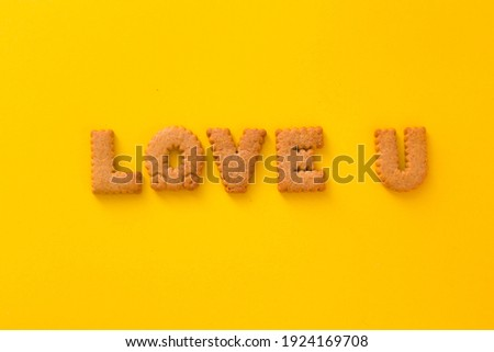 Word Love U in middle of the picture made of tasty crunchy cookies in form of English alphabet letters, textured bright yellow background, health, dieting and medical concept. Copy space big letters