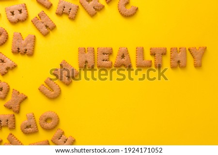 Word UnHealthy in the middle of the picture made of tasty crunchy cookies in form of big English alphabet letters, textured bright yellow background, health, dieting and medical concept. Copy space