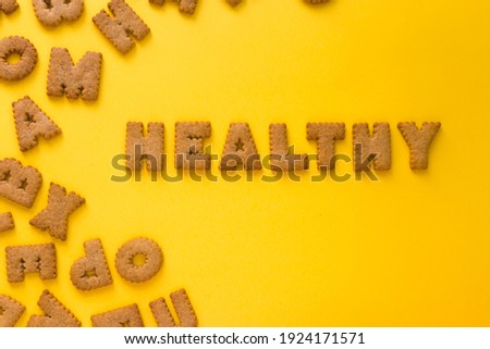 Word Healthy in the middle of the picture made of tasty crunchy cookies in form of big huge English alphabet letters, textured bright yellow background, health, dieting and medical concept. Copy space