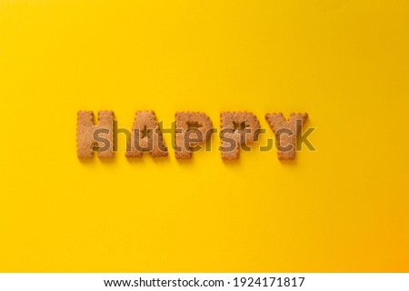 Word Happy in the middle of the picture made of tasty crunchy cookies in form of big huge English alphabet letters, textured bright yellow background, health, dieting and medical concept. Copy space