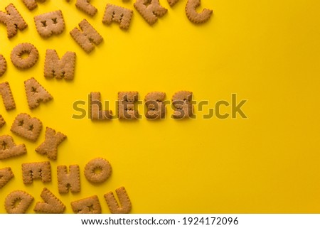 Word Less in the middle of the picture made of tasty crunchy cookies in form of big huge English alphabet letters, textured bright yellow background, health, dieting and medical concept. Copy space