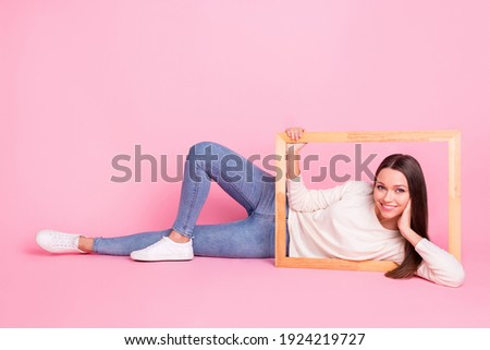 Photo of sweet funny young woman wear white clothes lying floor holding wooden photo frame isolated pink color background