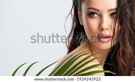 Young beautiful woman with healthy skin of face and palm leaves. Closeup fresh face of an attractive caucasian girl with green plants. Model with bright brown eye makeup. Skin care concept.  Royalty-Free Stock Photo #1924243922