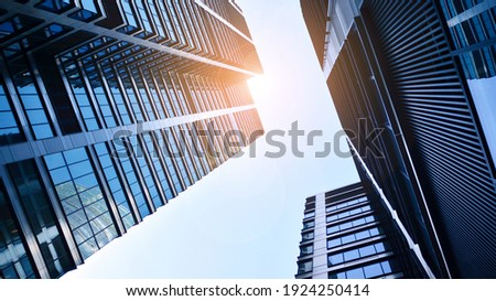Bottom view of modern skyscrapers in business district against blue sky. Looking up at business buildings in downtown. Rising sun on the horizon. Royalty-Free Stock Photo #1924250414