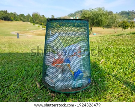 A rubbish bin with garbage at the golf course in blurry background.