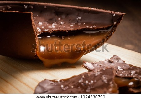 Cracked chocolate easter egg with flower of salt, stuffed with dulce de leche (dripping) on a wooden stand on a wooden table. Royalty-Free Stock Photo #1924330790