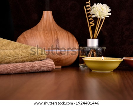 Flower and wooden scented stick stock images. Scented stick, wooden humidifier and candles close-up. Spa and wellness setting images. Spa still life with interior fragrance sticks stock photo