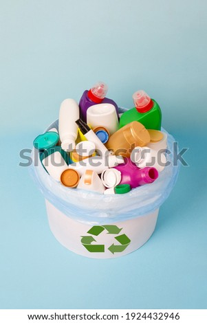 separate collection of sorted HDPE bottles from cosmetics and detergents in bucket for recycling. High-Density Polyethylene recyclable bottles on blue background. Plastic garbage. Save the plane Royalty-Free Stock Photo #1924432946