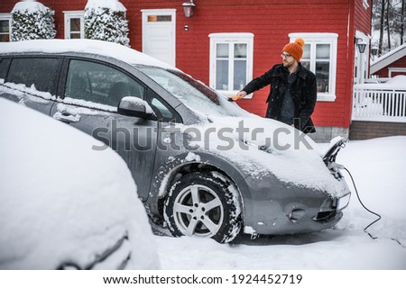 grey   electric car with Scandinavian house in the background. A nerdy guy with brush is removing snow.