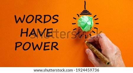 Words have power symbol. Businessman writing text 'Words have power', isolated on beautiful orange background. Light bulb icon. Business and words have power concept, copy space.