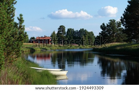 A picture of rural Swedish countryside. A traditional red house (stuga) in the background, and a boat on a lake. An idyllic landscape of Dalarna, Sweden. A summer view of Malung. Royalty-Free Stock Photo #1924493309