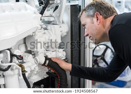 Caucasian Male Superyacht Engineer working on the engine room, inspecting the generator Royalty-Free Stock Photo #1924508567