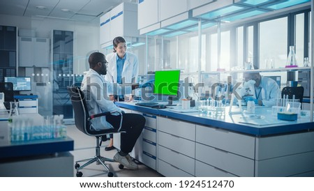 Modern Medical Research Laboratory: Two Scientists Use Computer with Green Chroma Key Screen, Specialists Discuss Innovative Technology. Advanced Scientific Lab for Medicine, Biotechnology