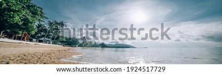 Tropical utterance landscape. Sea coast at sunrise. The sun rises over a sandy deserted beach on a tropical island. Royalty-Free Stock Photo #1924517729