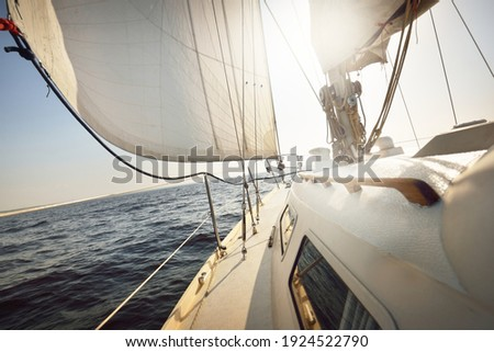 White sloop rigged yacht sailing in an open sea at sunset. Clear sky. A view from the deck to the bow, mast, sails. Transportation, travel, cruise, sport, recreation, leisure activity, racing, regatta Royalty-Free Stock Photo #1924522790