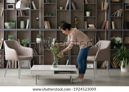 Young Indian female renter or tenant decorate cozy modern home or apartment. Millennial mixed race woman take care of flowers, involved in living room decoration. Interior design, rent concept. Royalty-Free Stock Photo #1924523009