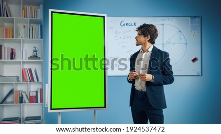 Portrait of Friendly Teacher Explains Lesson to a Classroom, Uses Green Screen Digital Whiteboard. Successful Businessman Talks about Project Growth Uses Chroma Key Digital Blackboard