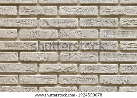 Textured beige brick wall, stone texture. decorative tiles for wall decoration. Background,  beige decorative brick. loft decor style. structural surface, imitates old brick Royalty-Free Stock Photo #1924550078