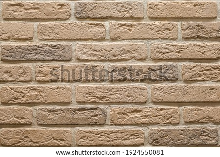 Textured beige brick wall, stone texture. decorative tiles for wall decoration. Background,  beige decorative brick. loft decor style. structural surface, imitates old brick Royalty-Free Stock Photo #1924550081