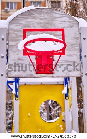 Basket for playing basketball on the playground against the background of a multi-storey building in the winter season