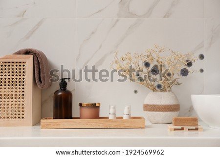 Personal hygiene products and toiletries on table near white wall in bathroom Royalty-Free Stock Photo #1924569962