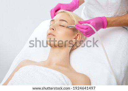 The cosmetologist makes the procedure Microdermabrasion of the face skin of a beautiful girl in a beauty salon.Cosmetology and professional skin care. Royalty-Free Stock Photo #1924641497