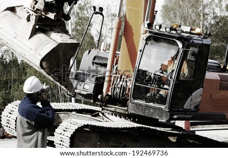 building worker directing large bulldozer and driver #192469736
