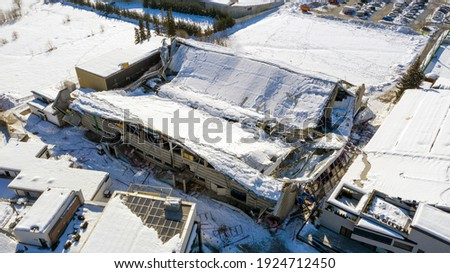 The roof collapsed under the weight of snow. Aerial view of damaged falling roof inside a publica city area. Large collapsed condominium or industrial company. View from above with a drone Royalty-Free Stock Photo #1924712450
