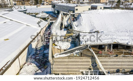 The roof collapsed under the weight of snow. Aerial view of damaged falling roof inside a publica city area. Large collapsed condominium or industrial company. View from above with a drone Royalty-Free Stock Photo #1924712456
