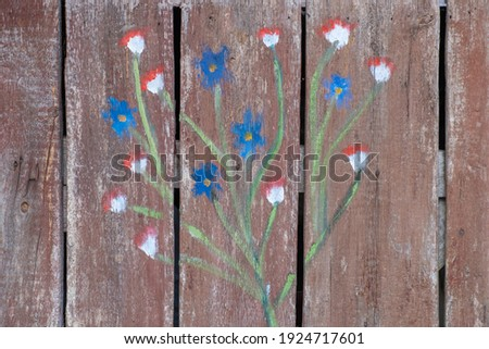 An old door with a cute floral ornament. Light burgundy aged, faded wood with stains. Textured background. Royalty-Free Stock Photo #1924717601