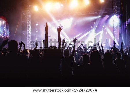 Rock concert, cheering crowd in front of bright colorful stage lights, Hands up with pleasure from the show Royalty-Free Stock Photo #1924729874