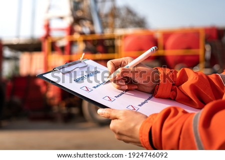 Action of safety office is writing on checklist paper during safety audit and risk verification at drilling site operation with blurred background of mount truck rig. Selective focus at hand. Royalty-Free Stock Photo #1924746092
