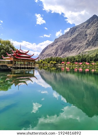 Shangrila resort in Shangrila lake at Kachura village, Skardu, Gilgit-Baltistan, Pakistan. Reflection of Shangrila resort, mountains, and sky with clouds in Kachura lake.