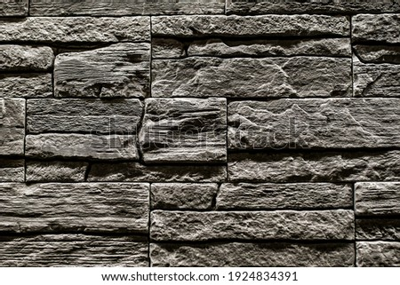 Black stone slate texture background, slate stone wall. decorative tiles for wall decoration. Black brick. loft decor style. structural surface imitating old brick. close-up of black stone wall Royalty-Free Stock Photo #1924834391