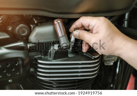 Mechanic Check motorcycle Spark Plug and Maintenance, inspection Prior to Installation in engine ignition at motorcycle garage.repair and maintenance motorcycle concept. Royalty-Free Stock Photo #1924919756