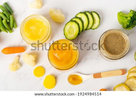 Variety of homemade baby vegetable and fruit puree, white marble background copy space top view Royalty-Free Stock Photo #1924984514