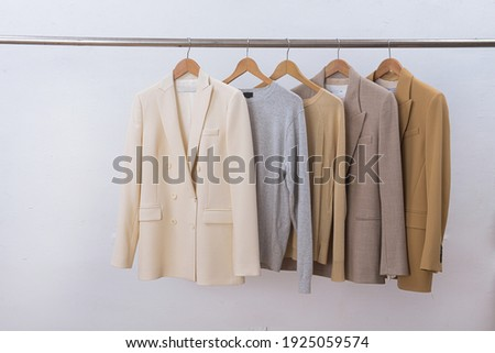 female, formal business four colour suit, jacket and sweater on hanger Royalty-Free Stock Photo #1925059574