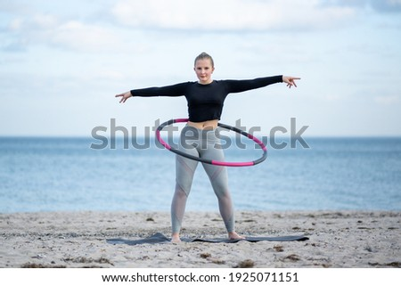 Young sporty woman is exercising with Hula hoop outdoors at the beach for healthy lifestyle concept. Royalty-Free Stock Photo #1925071151