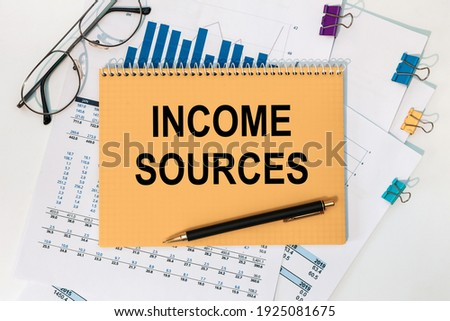 Notebook with the text Income sources on the office table among the stationery.