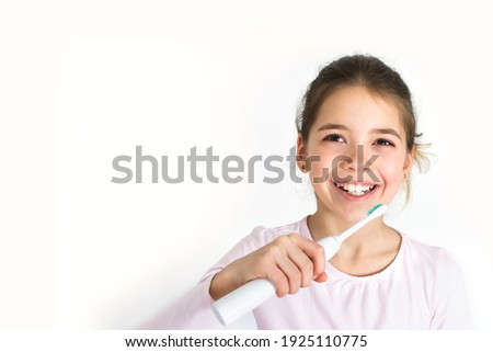 Child brushing their teeth with sonic electric toothbrush isolated on white background. Oral hygiene concept with copy space