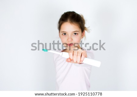 Child holding and showing sonic electric tooth brush isolated on white background. Oral hygiene and white teeth concept with copy space.