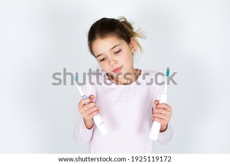 Young girl can´t decide between sonic and rotating oscillating toothbrush isotated on white background. Oral care and white teeth concept with copy space.